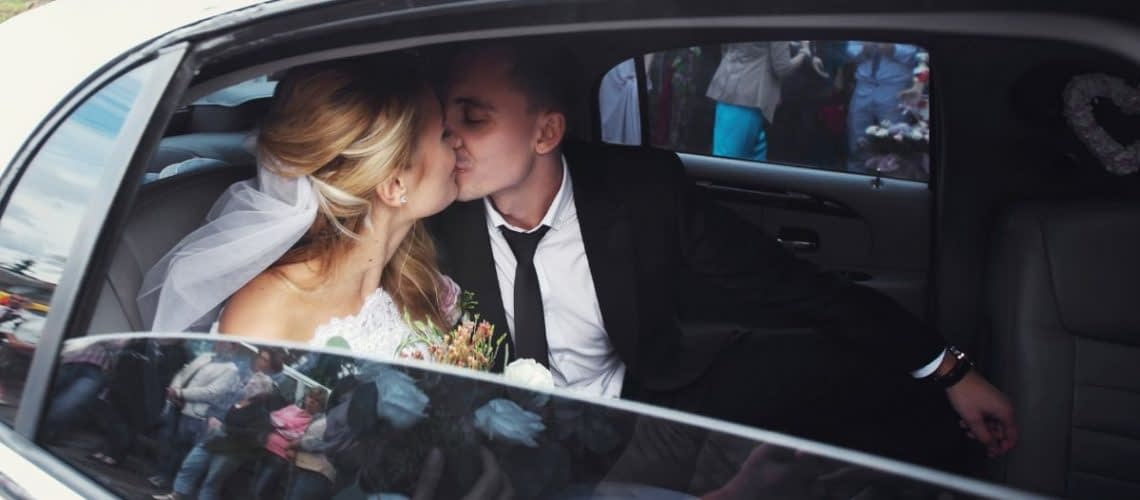 Newlyweds kissing in a white limo